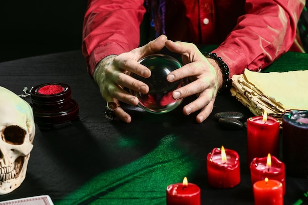 Male fortune teller with crystal ball at table, closeup