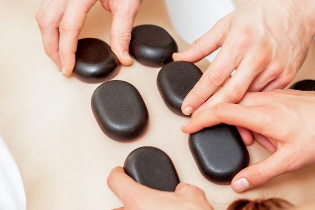 Мужчина в четыре руки кладет камни на женскую спину