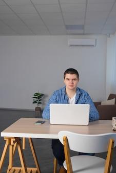 男性のフリーランサーは自宅でラップトップを使用しています。リモートワークのコンセプト