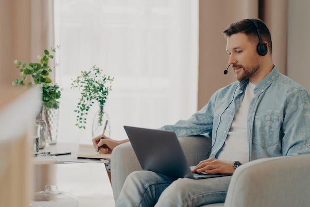 Male freelancer listens attentively tutorials how to start own business writes down information wears stereo headphones and laptop computer works online from home makes video call watches webinar
