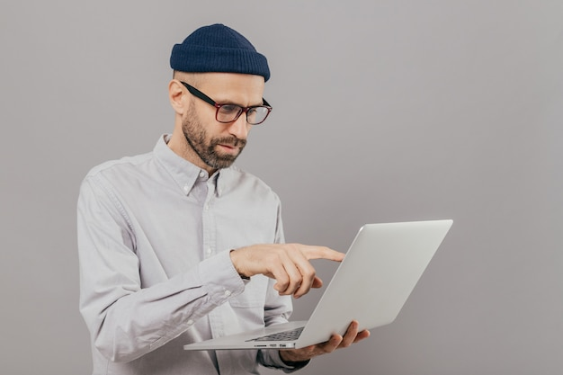 Male freelancer makes project work, points with index finger at screen of laptop computer