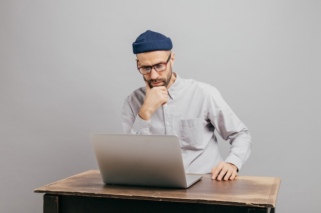 Male freelancer reads news in internet, looks attentively at laptop computer