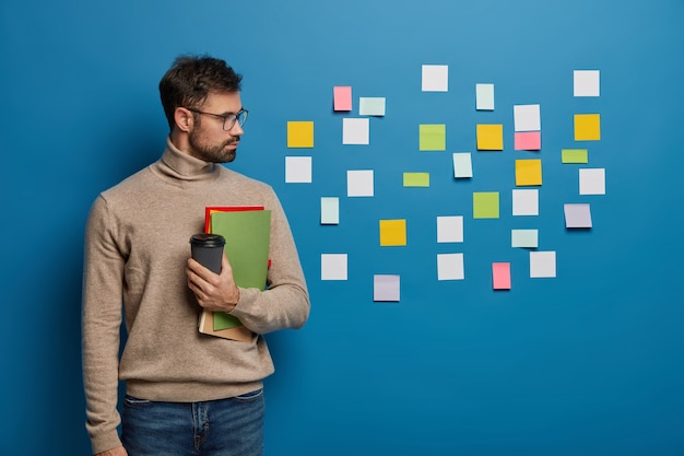 Male freelancer or student reads ideas written on paper notes stuck on blue wall, holds takeaway coffee and notepad, learns foreign words from colorful stickers