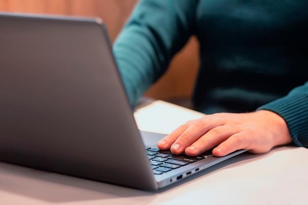 Фрилансер мужского пола, работающий на ноутбуке в офисе.