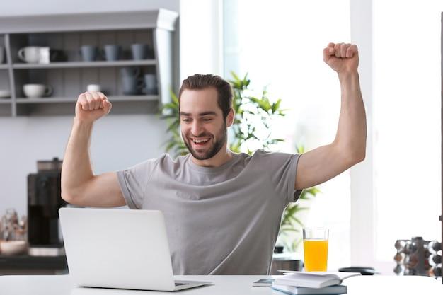 Фрилансер мужского пола, работающий с ноутбуком в домашнем офисе