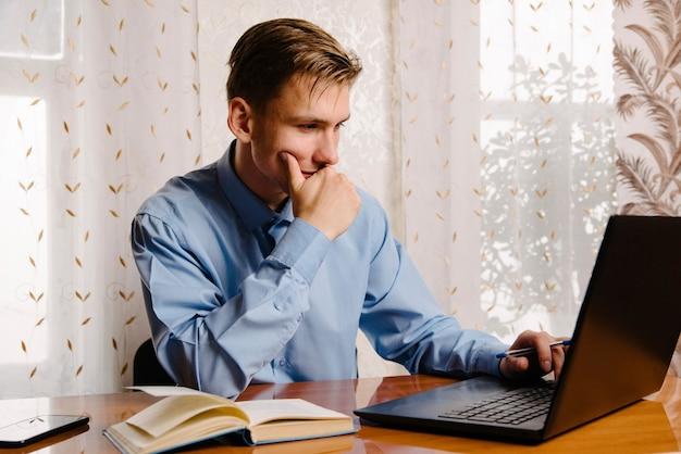 男性のフリーランサーは、自宅のデスクのラップトップでオンラインで作業します。自宅でラップトップを使用してビジネスマン。