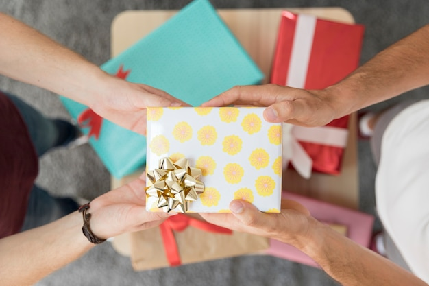 Male friend's hand holding gift box with golden ribbon bow