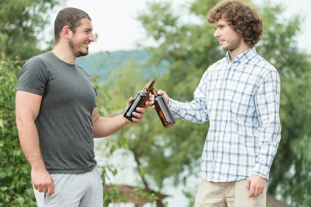 Male friends clinking bottles in nature