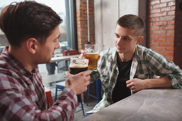 パブで飲んで、ビアグラスをチリンと鳴らす男性の友人