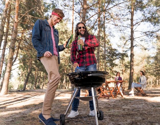 Amici maschi che bevono birra sopra il barbecue
