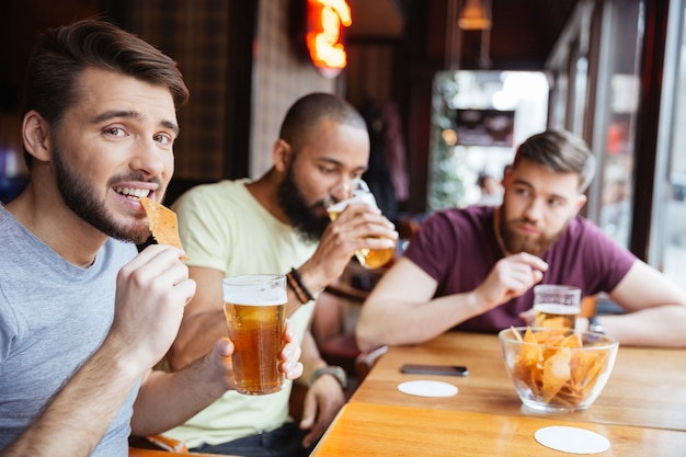 Male friends drinking beer and eating chips in pub