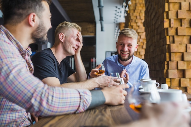 Male friends enjoying the evening drinks at restaurant