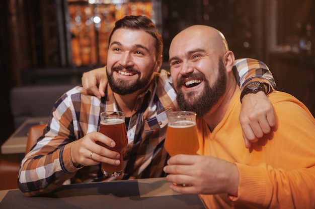Male friends hugging, holding up their beer glasses, celebrating at the bar