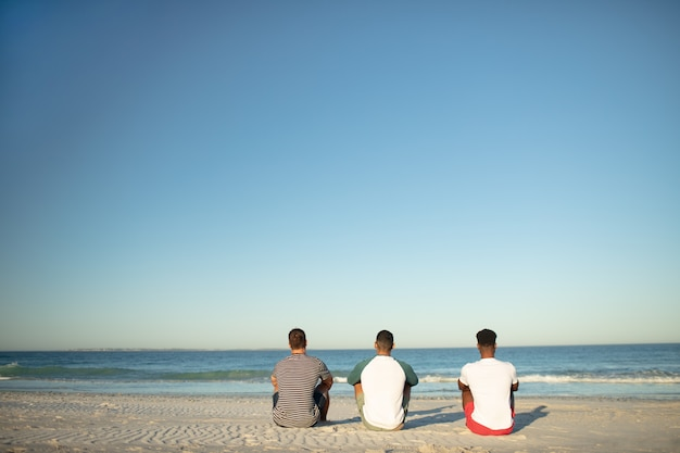 Male friends relaxing together on the beach