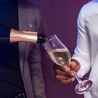 Amici maschi che condividono una bottiglia di champagne