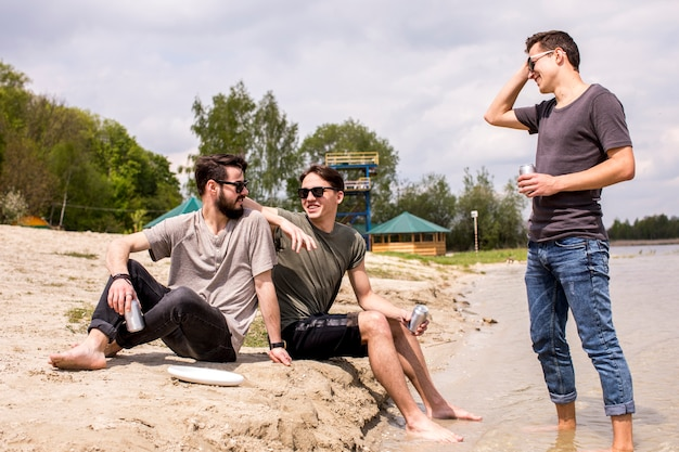 Male friends in sunglasses sitting on beach and talking