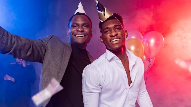 Друзья-мужчины в окружении воздушных шаров и конфетти
