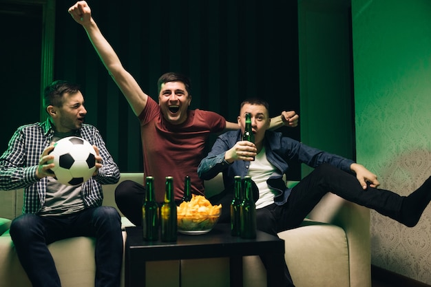 スポーツチャンネルを見ている男性の友人は、3人のハンサムな幸せな白人のフレンドリーな男性を集めました