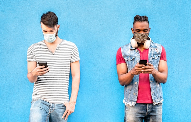 Male friends with face masks using tracking app with mobile smart phones