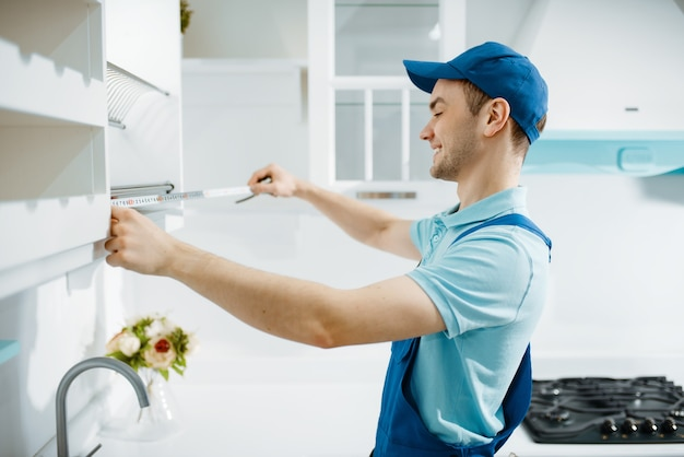 Male furniture maker in uniform measures table top in the kitchen. handyman installing garniture, repairing service at home