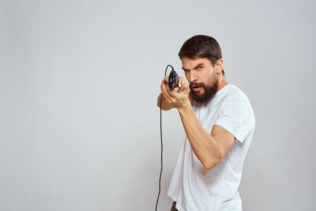 ヘッドフォンでジョイスティックを使ってコンソールをプレイする男性ゲーマー