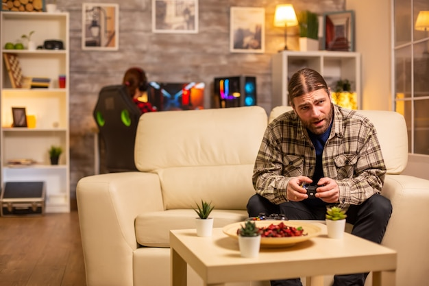 Male gamer playing video games on a console in the living room while sitting on the sofa