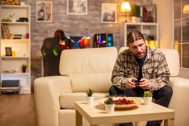 Геймер-мужчина играет в видеоигры на консоли в гостиной, сидя на диване