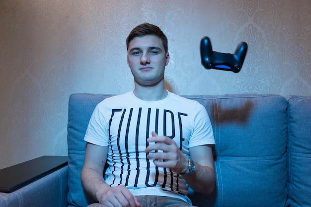 남자 게이머는 집 소파에서 텔레비전 앞에 앉아 게임을 한 후 콘솔을 버린다