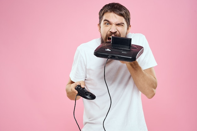 Male gamer with joysticks entertainment console and pink background