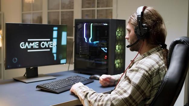 長い髪の男性ゲーマーは、シューティングゲームをプレイしているときに負けたとは信じられません。