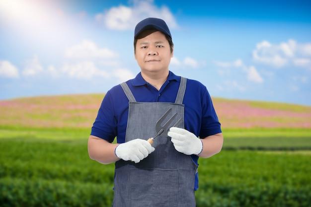 シャベルまたは園芸工具を持っている男性の庭師の手