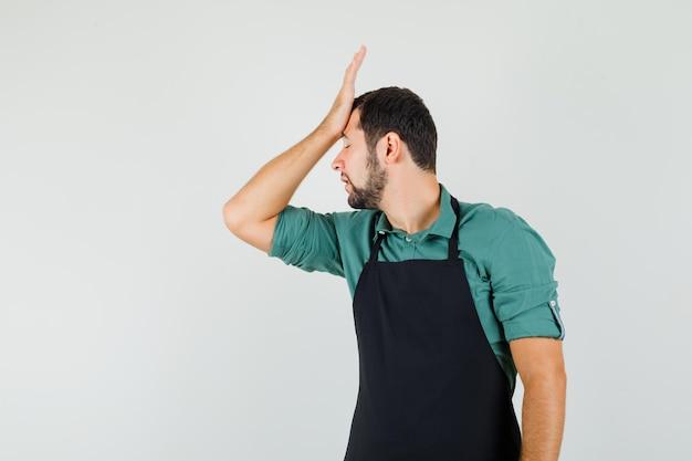 Tシャツ、エプロンで額に手を握り、忘れて見える男性の庭師。正面図。