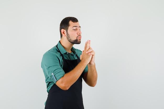 Tシャツを着た男性の庭師、手で作られた銃を吹くエプロン、自信を持って、正面図。