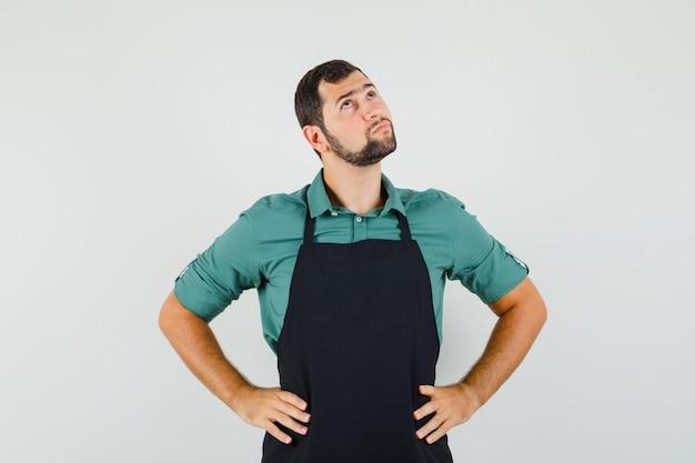 Giardiniere maschio alzando lo sguardo con le mani sulla vita in maglietta, grembiule e guardando pensieroso. vista frontale.