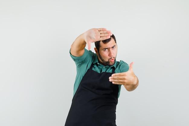 Giardiniere maschio che fa gesto di cornice in maglietta, vista frontale del grembiule.