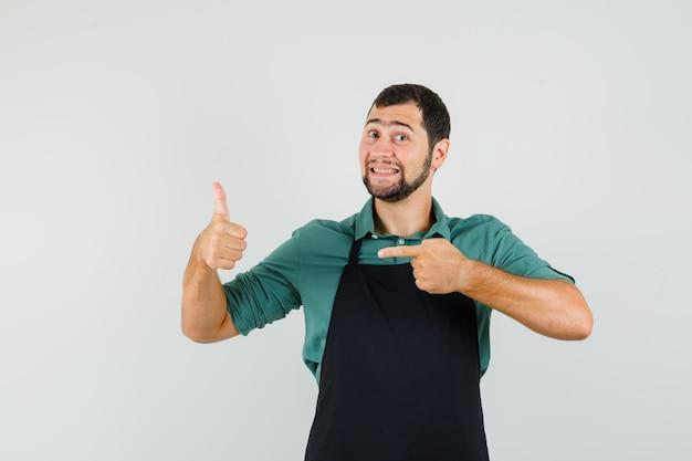 Giardiniere maschio che indica il pollice in su in maglietta, grembiule e sembra felice. vista frontale.