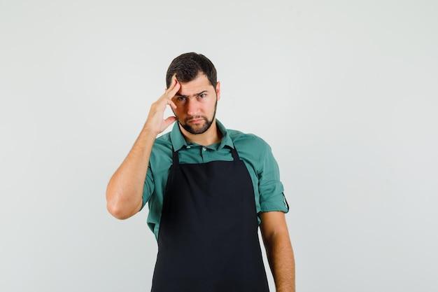 Giardiniere maschio in piedi in posa di pensiero in t-shirt, grembiule e guardando sensato, vista frontale.