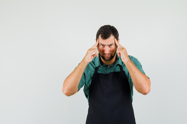 Giardiniere maschio in maglietta, grembiule che tiene le dita sulle tempie e sembra serio, vista frontale.