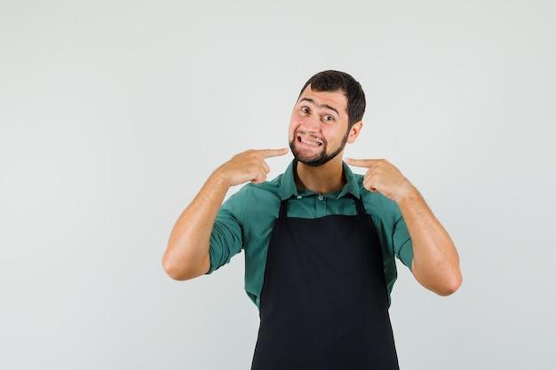 Giardiniere maschio in maglietta, grembiule che indica i suoi denti, vista frontale.