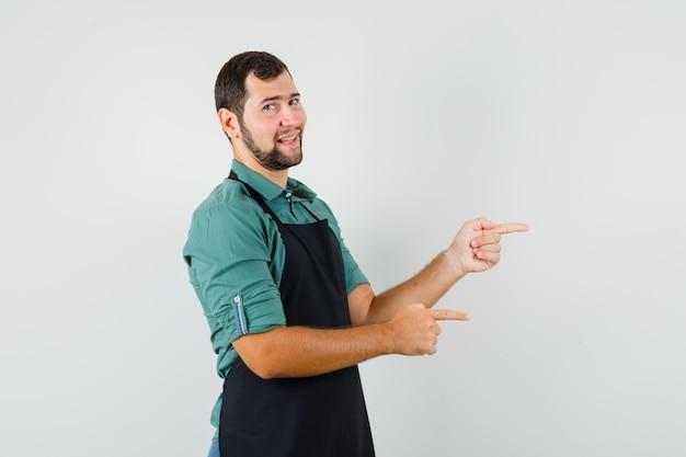 Giardiniere maschio in maglietta, grembiule che punta al lato e sembra allegro, vista frontale.