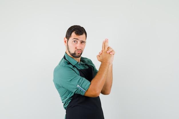 Giardiniere maschio in maglietta, grembiule che mostra il gesto della pistola di tiro e sembra sicuro, vista frontale.