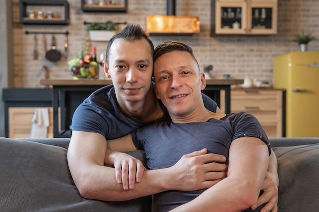 自宅でカメラを抱き締めて見ている男性の同性愛者のカップル
