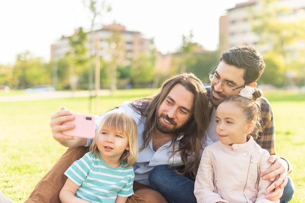 芝生の上に座っている子供たちと一緒に自分撮りをしている男性の同性愛者のカップル