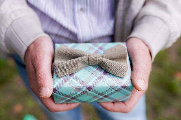 Мужской подарочная коробка в мужской руке с серым бантом