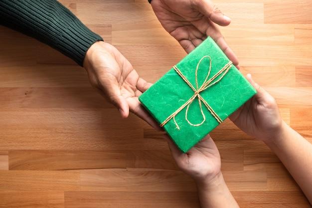 남성은 나무 테이블에 여성에게 선물을 제공합니다.