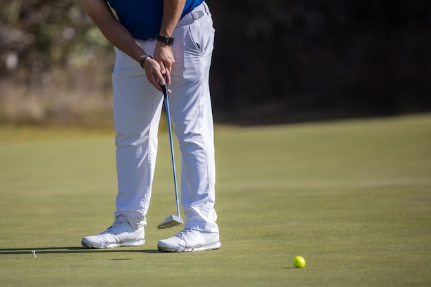 Male golf player hitting the ball  wearing white shoes