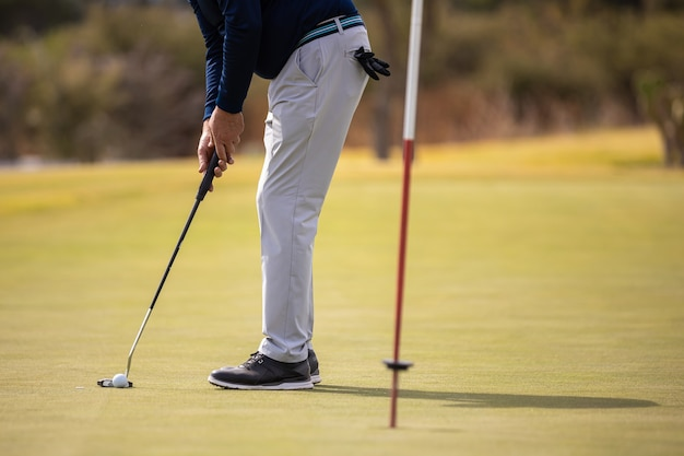 Male golf player hitting the ball