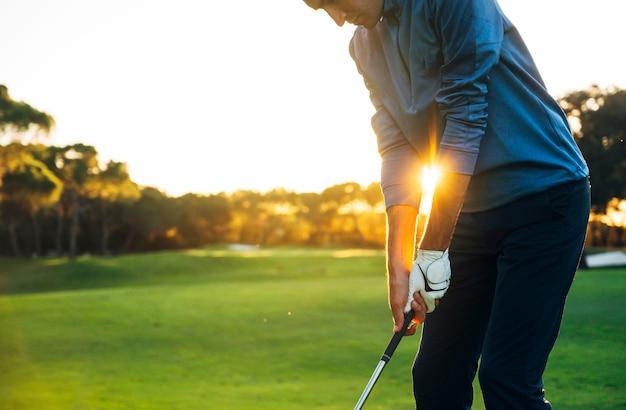 Игрок в гольф мужского пола, отрывающийся от мяча для гольфа от тройника до красивого заката