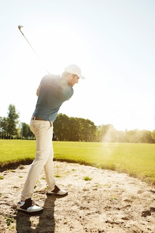 Male golfer hitting ball out of a sand trap