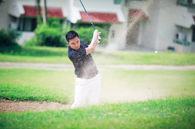 Male golfer hitting out of a sand trapgolfer shot ball from sand bunker at golf course in the sunny day